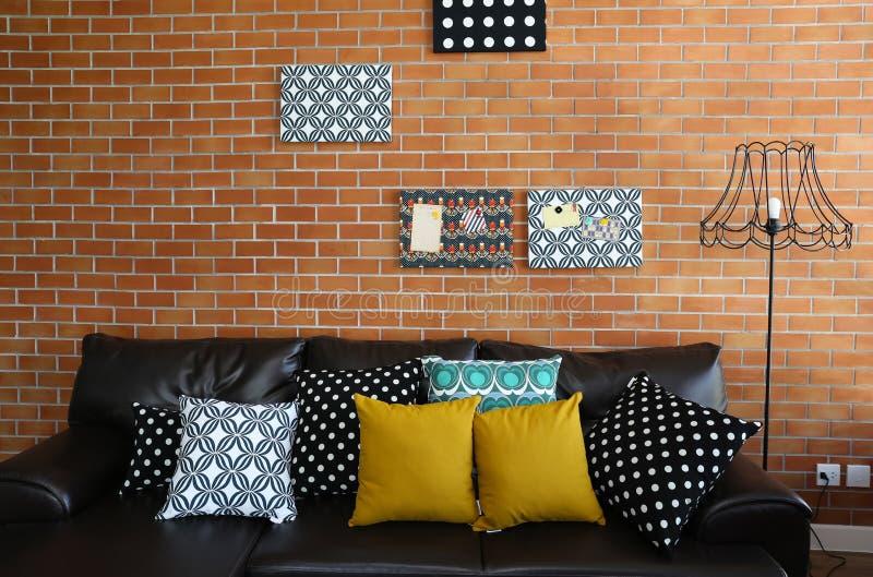 Almohadas coloridas en un sofá con la pared de ladrillo fotografía de archivo