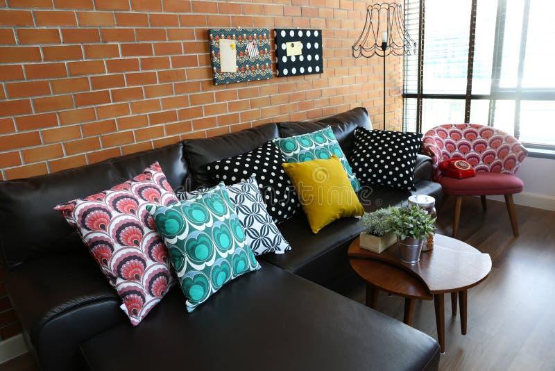 Almohadas coloridas en un sofá con la pared de ladrillo imagenes de archivo