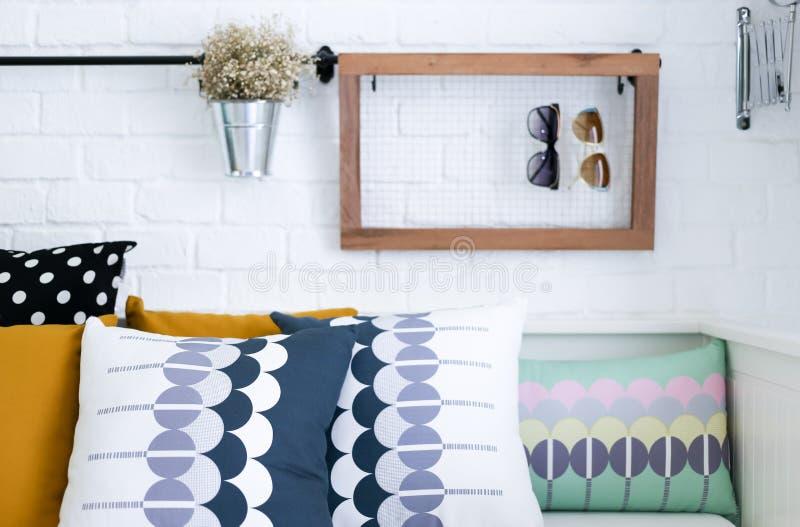 Almohadas coloridas en un sofá con la pared de ladrillo blanca i fotos de archivo libres de regalías