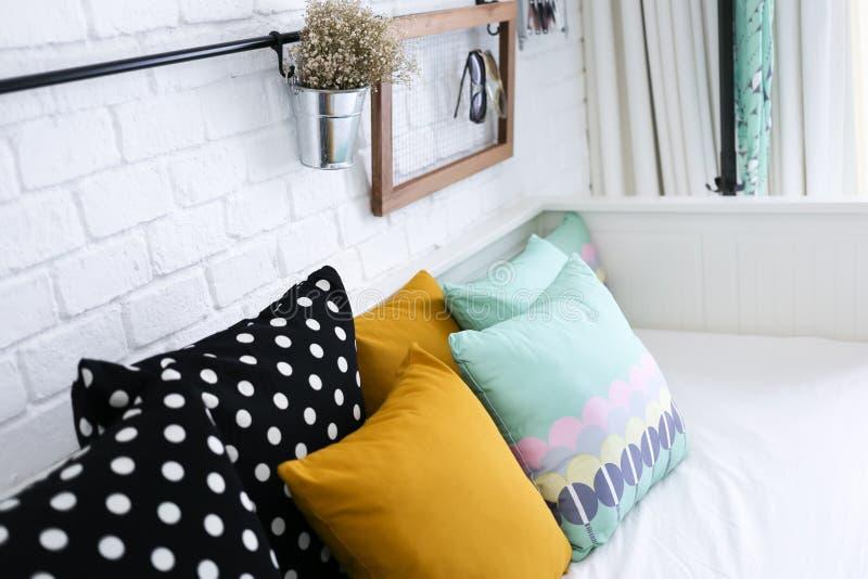 Almohadas coloridas en un sofá con la pared de ladrillo blanca i imagen de archivo libre de regalías