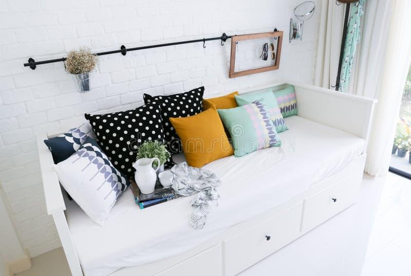 Almohadas coloridas en un sofá con la pared de ladrillo blanca i foto de archivo libre de regalías