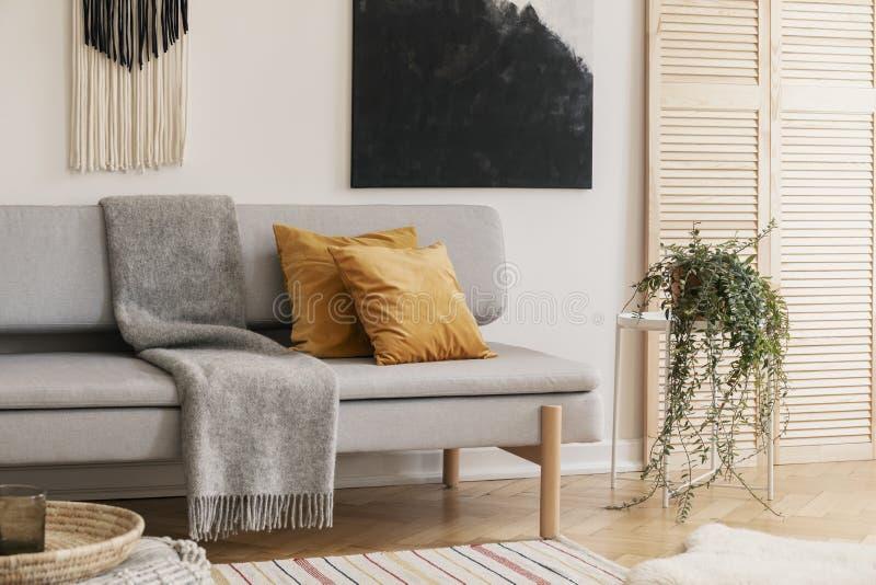 Almohadas de Brown y manta gris en el sofá en sala de estar imágenes de archivo libres de regalías