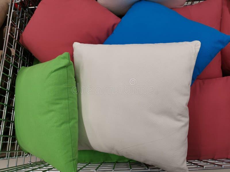 Almohadas decorativas coloreadas multi en una cesta imagen de archivo libre de regalías