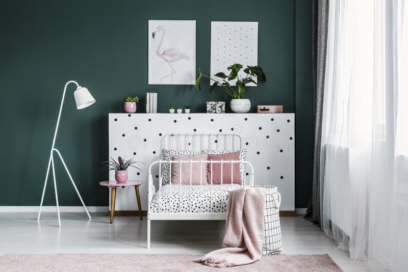 Almohadas en un sistema de la sola cama en una pared punteada al lado de una tabla y fotos de archivo libres de regalías