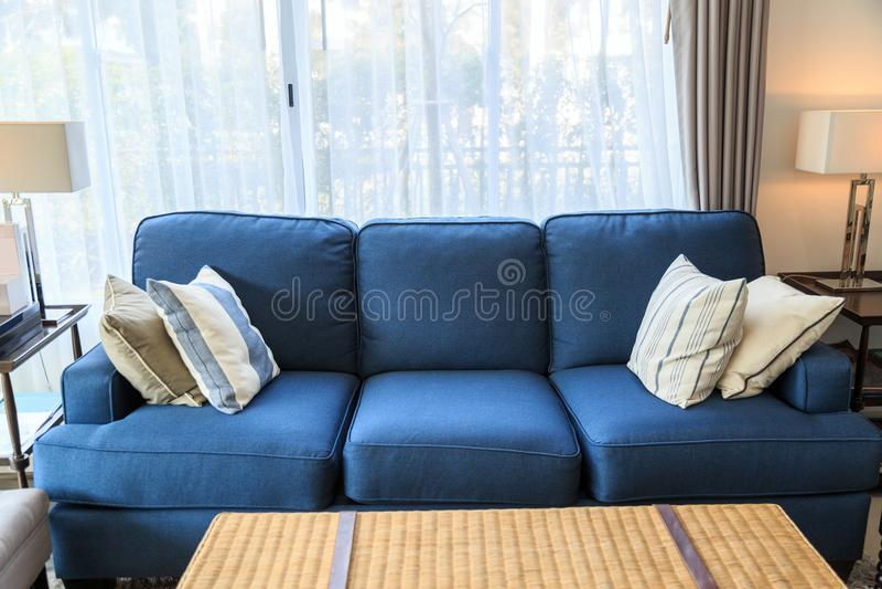 Almohadas en un sofá azul con la lámpara en sala de estar fotos de archivo