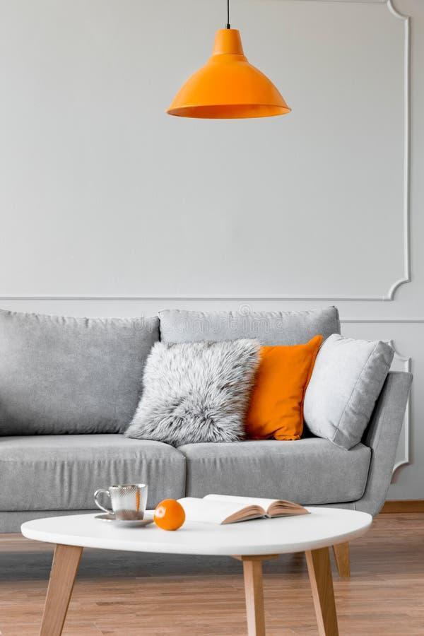 Almohadas en un sof?, una l?mpara anaranjada y una mesa de centro en un interior de la sala de estar Foto verdadera fotos de archivo libres de regalías