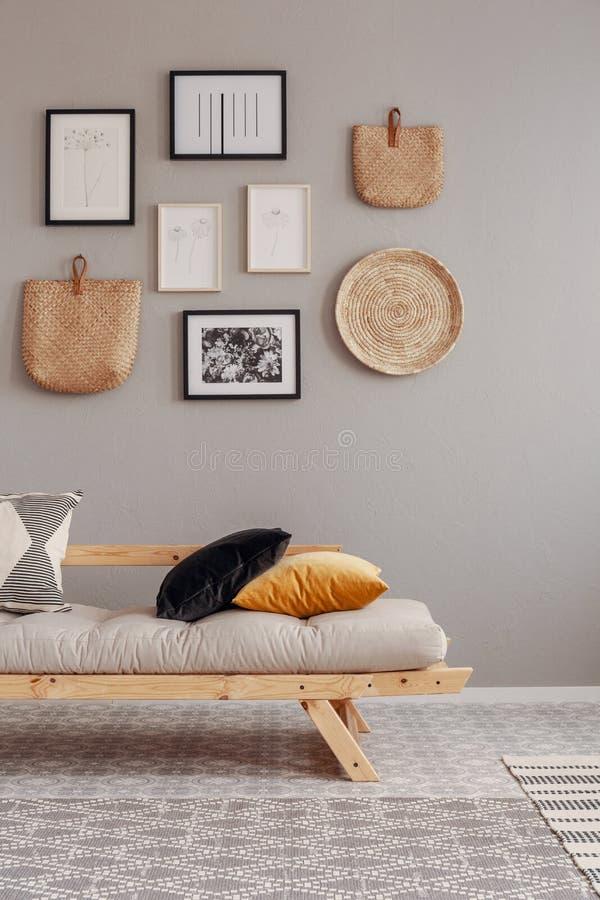 Almohadas modeladas, amarillas y negras en futon escandinavo beige en interior imponente de la sala de estar foto de archivo