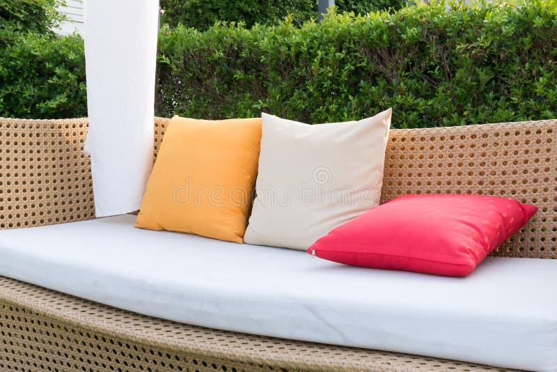 Almohadas modernas del mimbre y del color del sofá imagenes de archivo