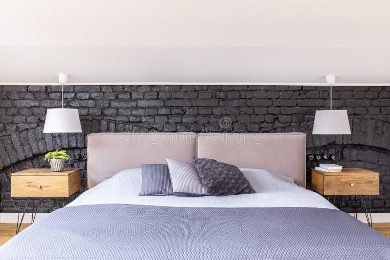 Almohadas monocromáticas en cama gigante fotos de archivo