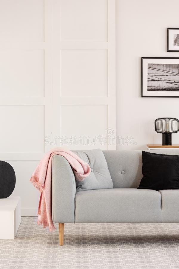 Almohadas negras y grises en el sof? escandinavo en el interior blanco de la sala de estar, espacio de la copia en la pared vac?a imágenes de archivo libres de regalías