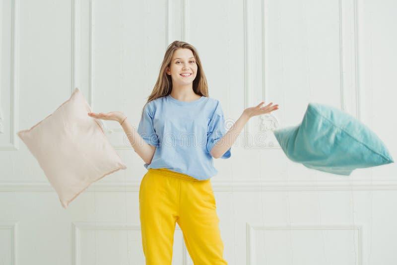 Almohadas que lanzan sonrientes de la muchacha Mujer juguetona feliz en pijama fotos de archivo libres de regalías