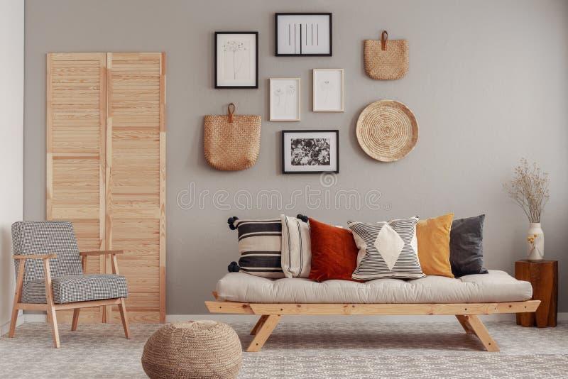 Almohadas rojas, amarillas y modeladas en el sofá escandinavo elegante de la sala de estar imagen de archivo libre de regalías