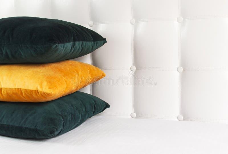 Almohadas suaves decorativas brillantes en cama en el fondo del cabecero acolchado de cuero Almohada esmeralda y anaranjada, part fotos de archivo