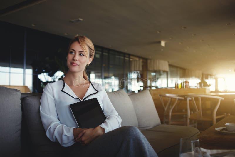 Almohadilla táctil que se sostiene femenina joven pensativa con la pantalla en blanco del espacio de la copia para su mensaje de  imagenes de archivo