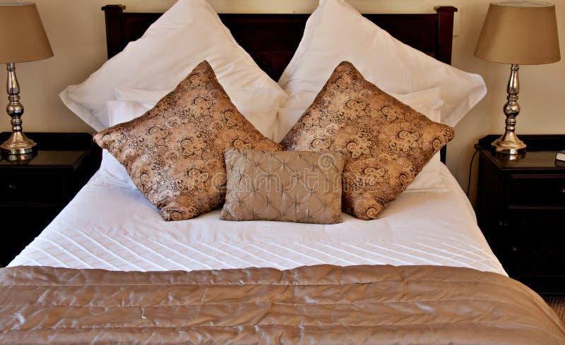 Almohadillas del oro en la cama blanca foto de archivo libre de regalías