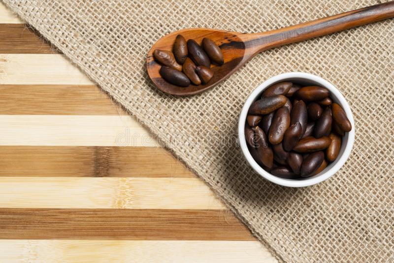 Almond baru inside brown pottery and wooden spoon on bamboo wooden background.  royalty free stock photography