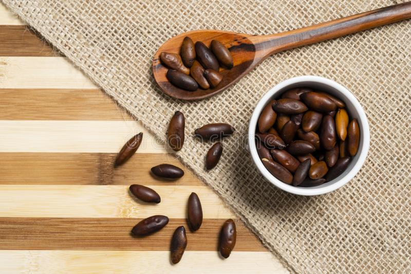Almond baru inside brown pottery and wooden spoon on bamboo wooden background.  royalty free stock photos