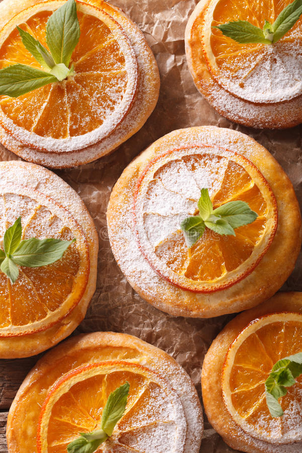 Almond biscuits with orange slices and mint on a table macro. Vertical top view. Almond biscuits with orange slices and mint on a table macro. Vertical view from royalty free stock photos