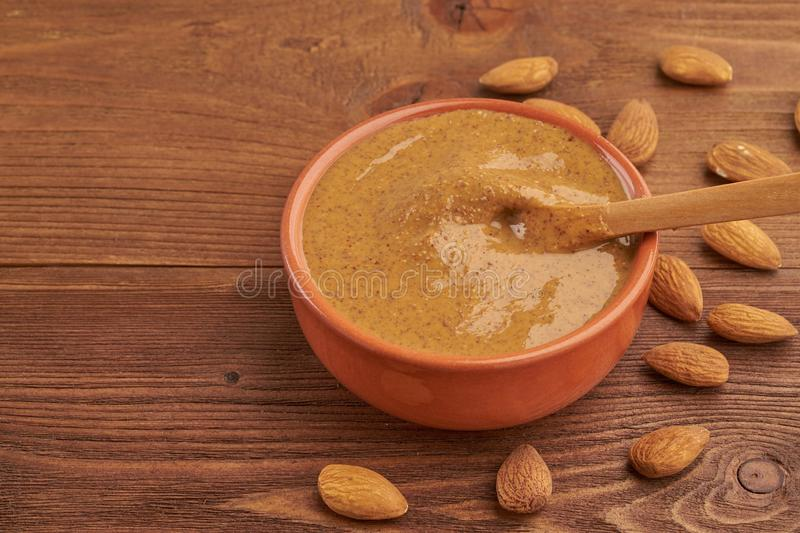 Almond butter, raw food paste made from grinding almonds into a nut butter, crunchy and stir, dark brown wooden table, copy space stock photos