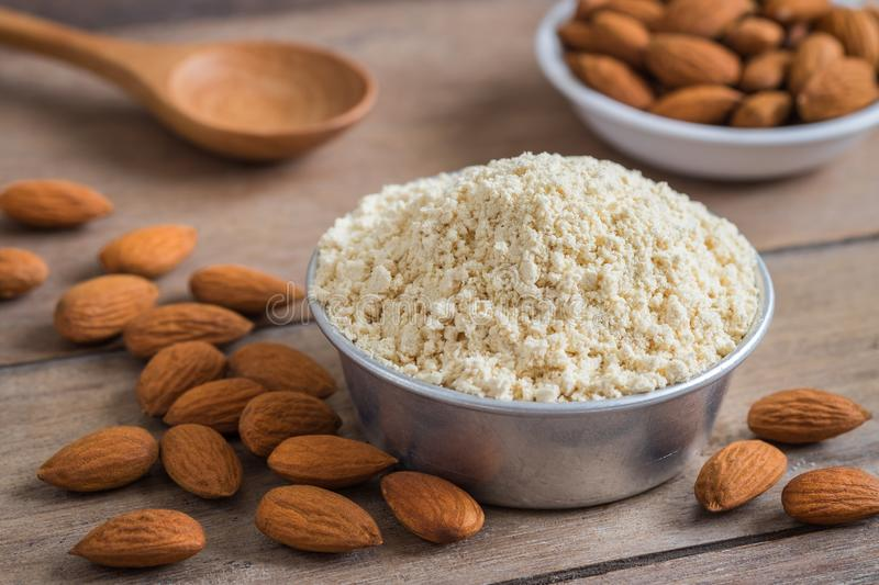 Almond flour in bowl and almonds on wooden table royalty free stock image
