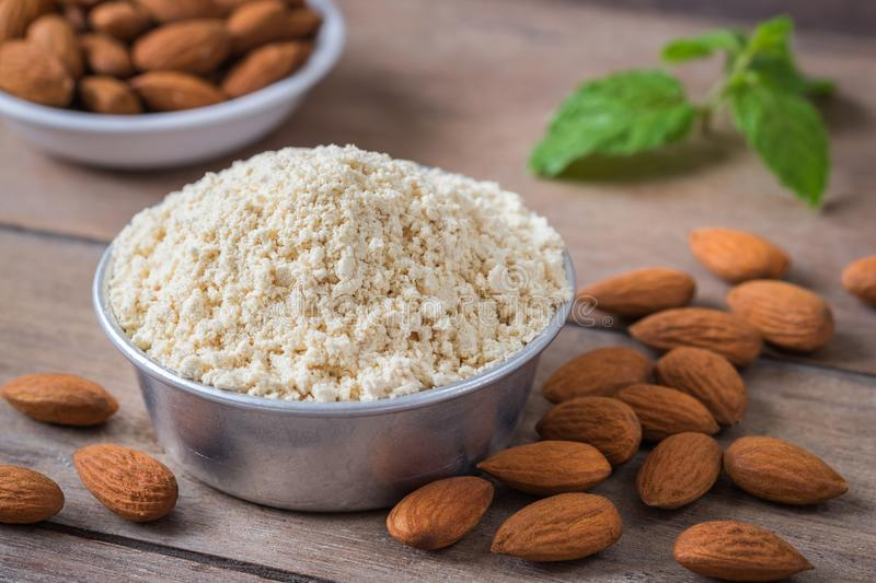 Almond flour in bowl and almonds on wooden table royalty free stock photos