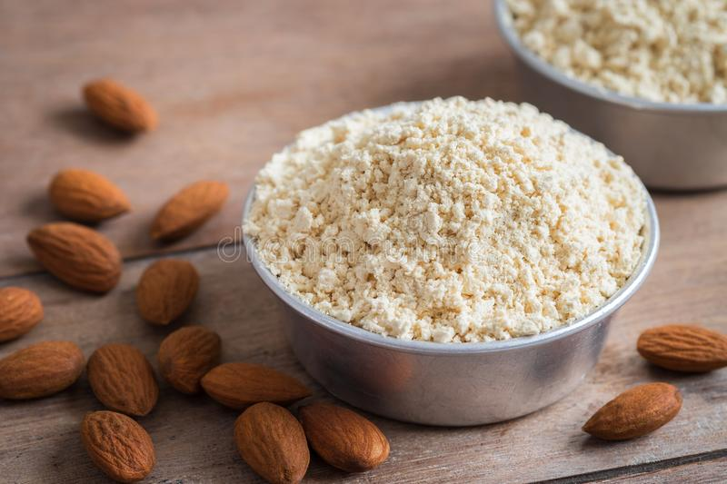 Almond flour in bowl and almonds on wooden table royalty free stock photography