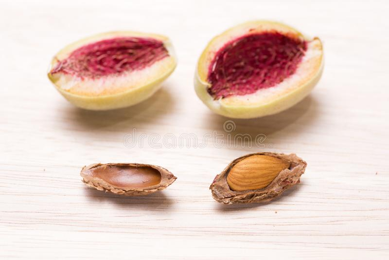 Almond fruit with seed. Almond fruit divided in half and seed with hard shell on a wooden table stock images
