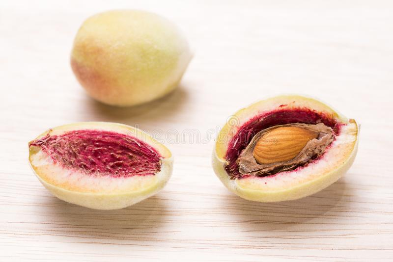 Almond fruit with seed. Almond fruit divided in half with seed on a wooden table royalty free stock photos