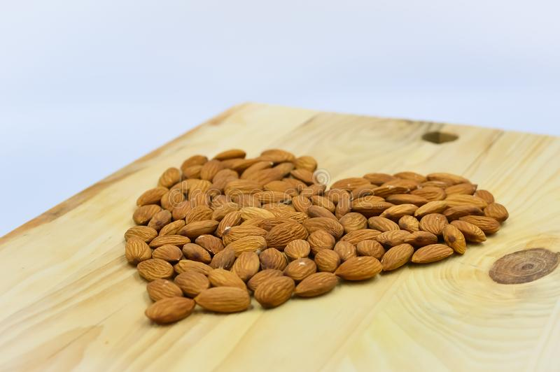 Almond heart on the wood. Raw almonds in shape of hart on the wooden background stock photography