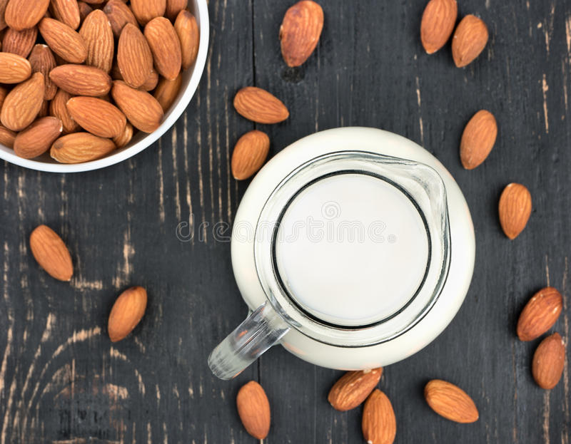 Almond milk. Bowl of nuts and almond milk on a dark table, top view royalty free stock photo