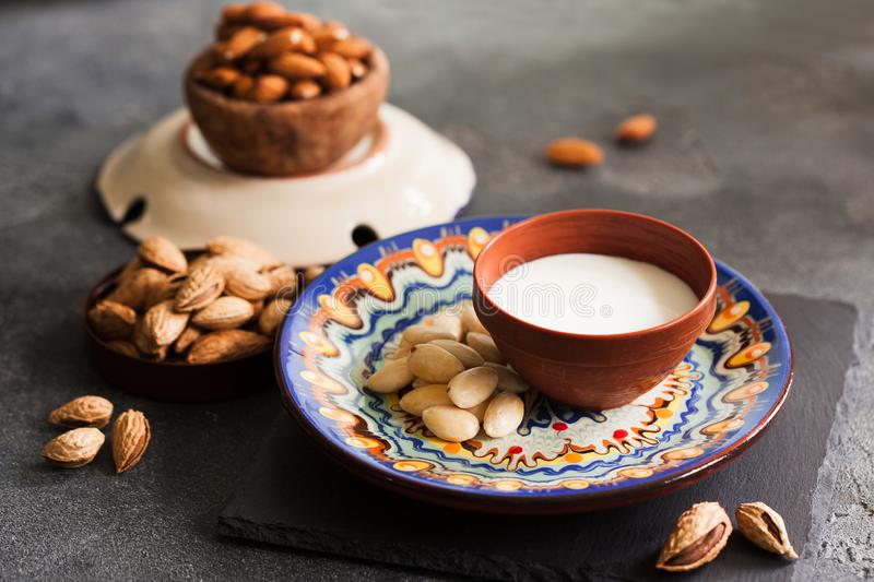 Almond milk in a clay pot and fresh nuts over dark slate background, selective focus. Dairy-free, vegan healthy food concept royalty free stock photography