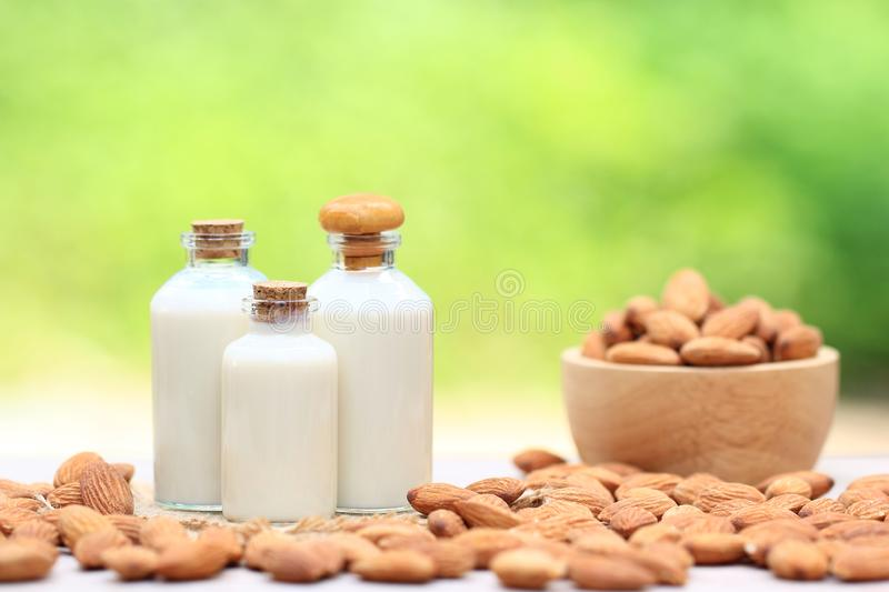 Almond milk in glass bottle with almonds in a bowl on the table blurred natural green background royalty free stock images