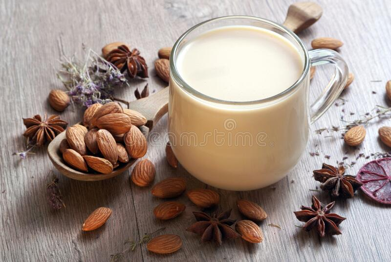 Almond milk in a glass and spices on a wooden table. Almonds in a wooden spoon and a glass of almond milk. top view royalty free stock photos