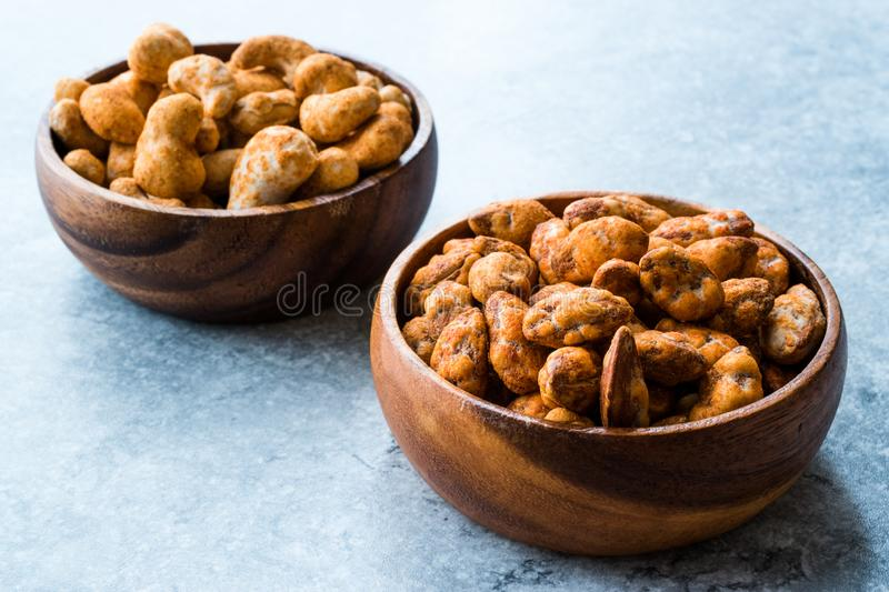 Almond Nuts with Barbeque Sauce and Spicy Cashew with Taco Spice in Wooden Bowl. royalty free stock images