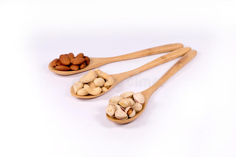 Almond nuts,cashew and pistachio in wooden spoon on white backg stock images