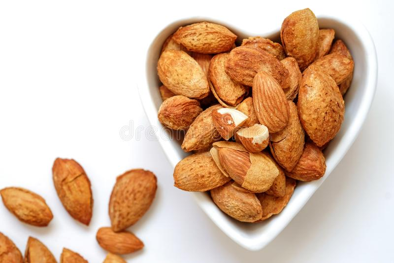 Almond nuts in the shell In a heart shaped bowl royalty free stock photo