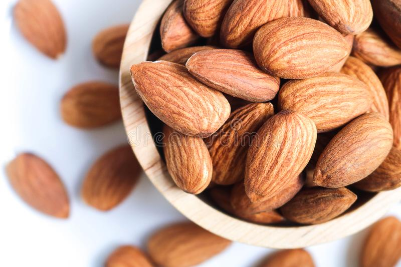 Almond nuts in wooden bowl on white background stock photography