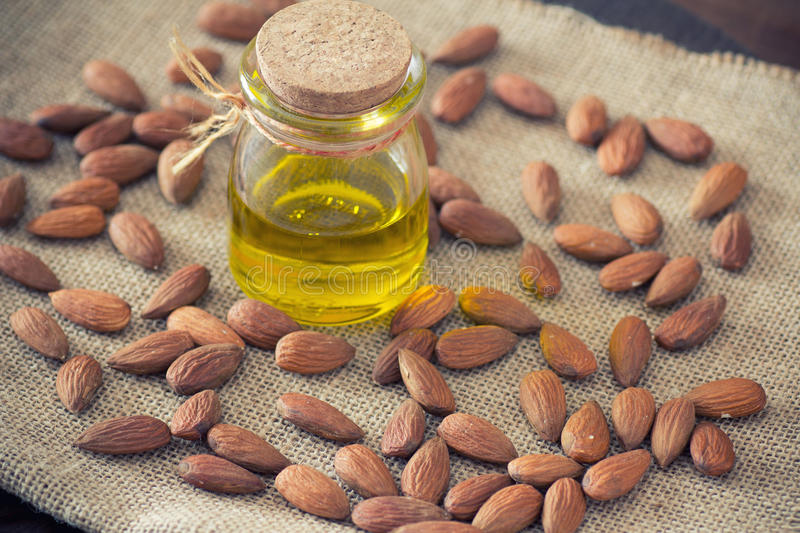 Almond oil. Almonds and almond oil on wooden table royalty free stock photos