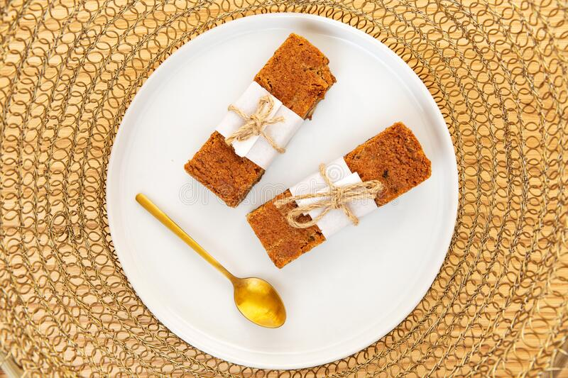 Almond and pecan nut financier cake with a golden spoon in a plate over a golden wire background, Flat lay, top view. Almond and pecan nut financier cake rolled royalty free stock photos