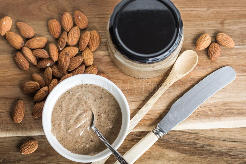 Almonds and Almond Nut Butter. Homemade Almond Nut Butter in a jar and small bowl, with almonds on wooden board stock photo