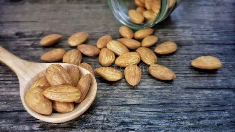 Almonds are beneficial to the heart. And reduce risk of heart disease. Almonds on wooden spoon isolated on wood background stock images