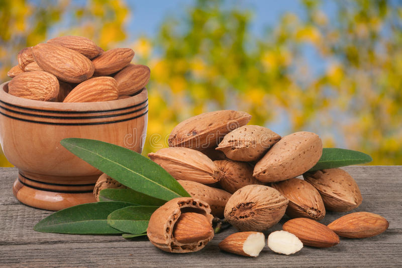 Almonds in a bowl on the old wooden board with blurred garden background.  stock photos