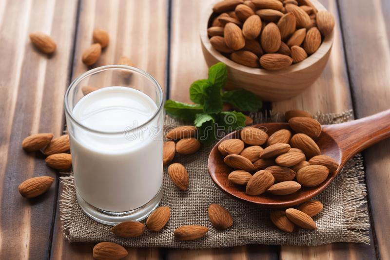 Almonds in bowl wood with spoon and milk on dark table background. Protein, plant, agriculture, fresh, dry, meal, eat, bag, energy, rustic, many, fruit, object royalty free stock photography