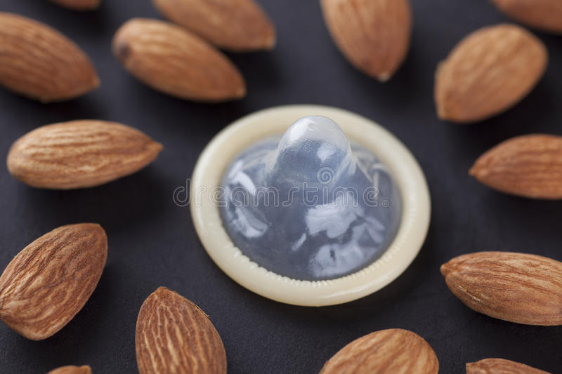 Almonds (Foods for Your Sex Life). Foods for Your Sex Life. Almonds and condom. Almonds can Improve your sex life (libido). Concept image about Impotence ( stock photo