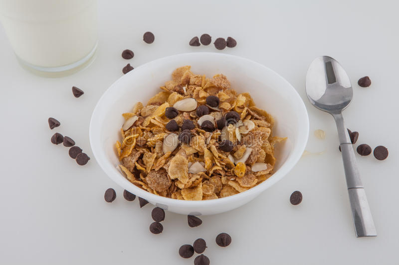 Almonds Oats cereal milk chocolate chips honey. Almonds Oats cereal glass of white milk chocolate chips honey sliver spoon white bowl royalty free stock images