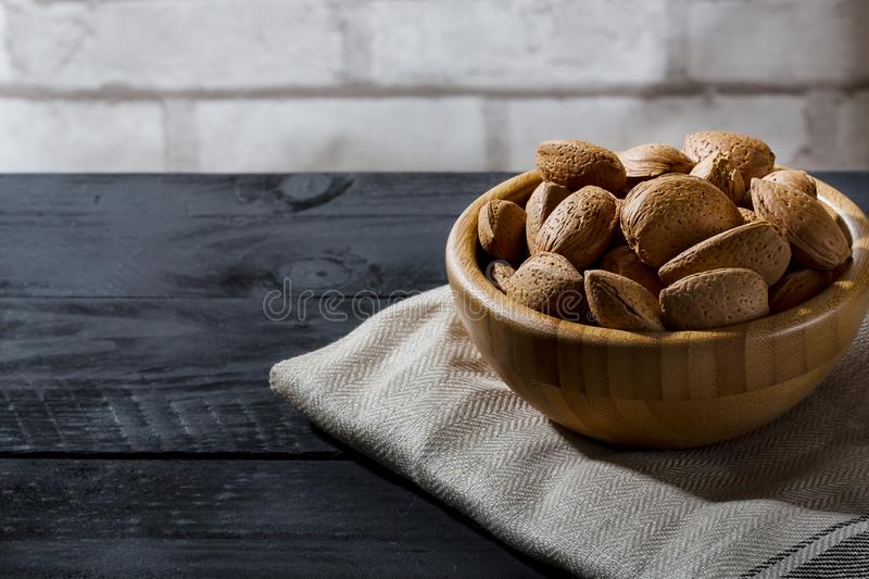 Almonds with shell in wooden bowls on slate background stock photos