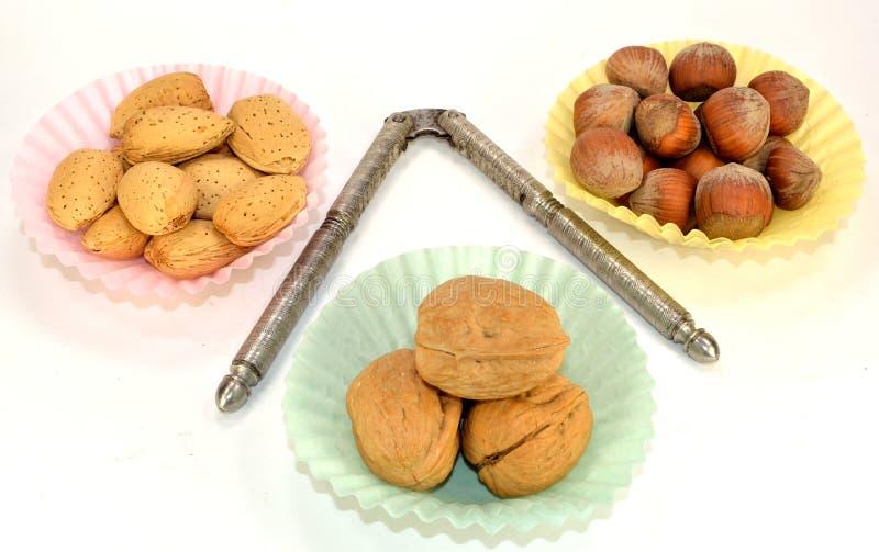 Almonds, Walnuts and Hazelnuts. Walnut, almonds and hazelnuts in paper cups with a nutcracker stock image