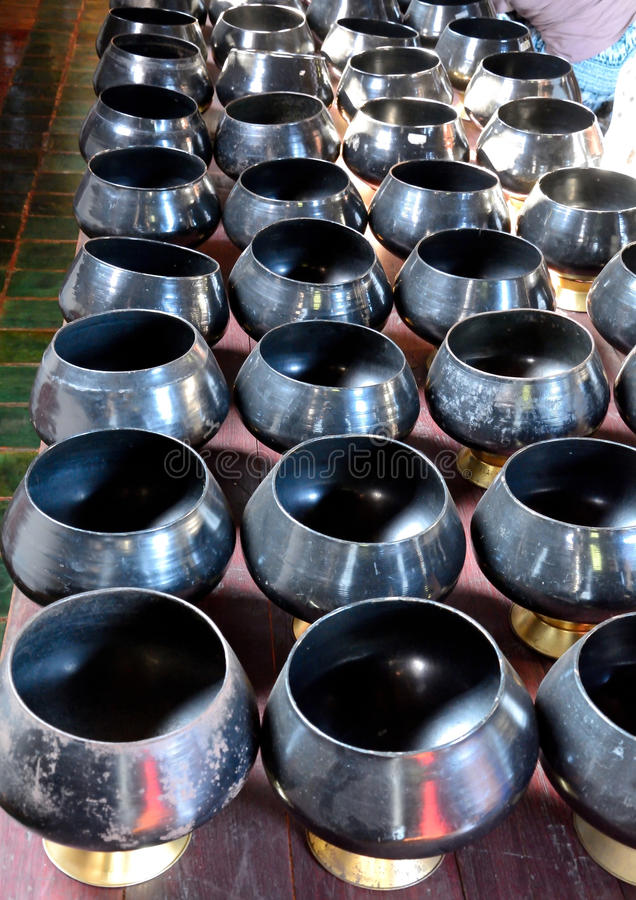 Alms long rows. Image alms long rows inside the temple as a container for the clergy, Thailand. And merit Black handmade A blacksmith Over high heat Than it is a stock images