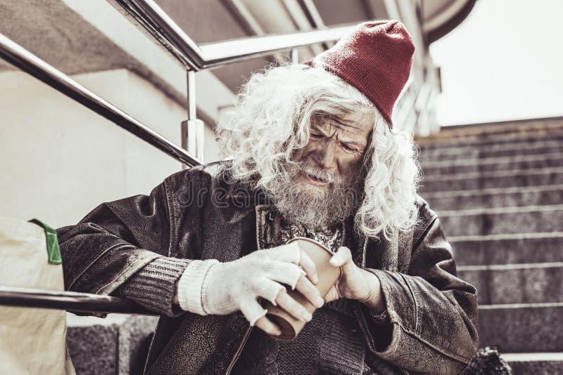 Almsman сидя и считая небольшие деньги получил в день стоковое изображение