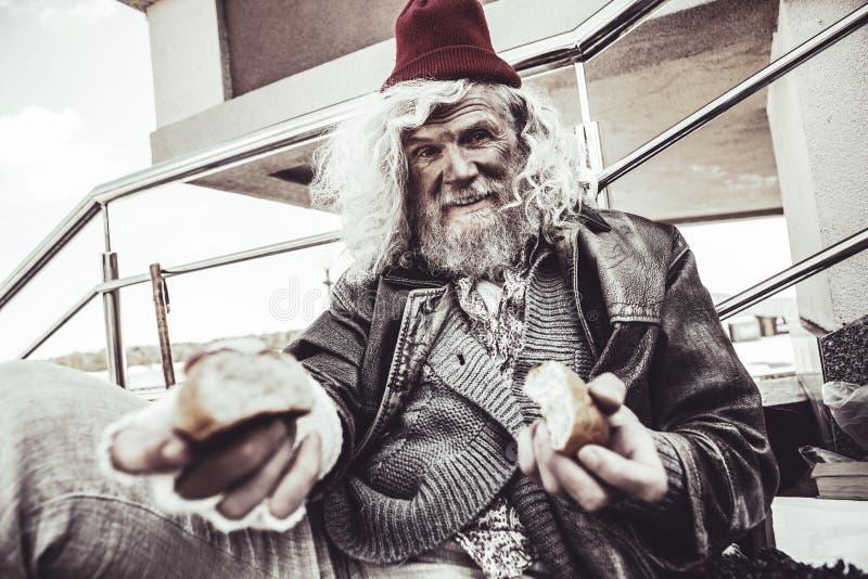 Almsman caucasien reposant et mangeant le petit pain qui il trouvant sur la rue photos libres de droits